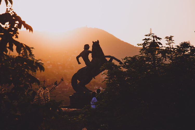Statues against mountains during sunset