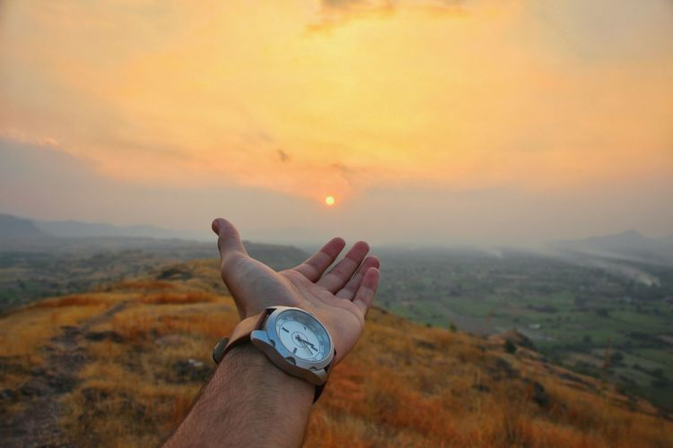 Cropped hand of man reaching sky during sunset