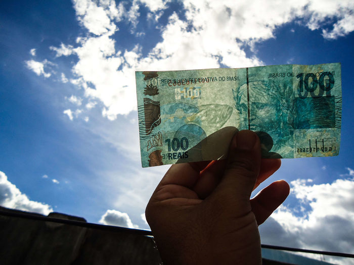 Cropped hand holding paper currency against sky