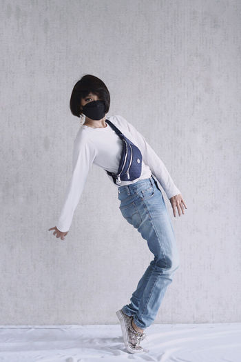 Full length of woman wearing mask dancing against wall