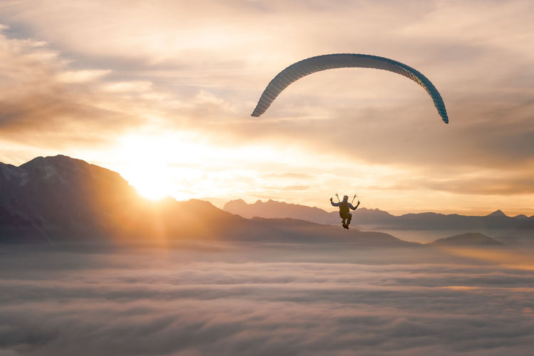 Man paragliding over clouds against cloudy sky during sunset