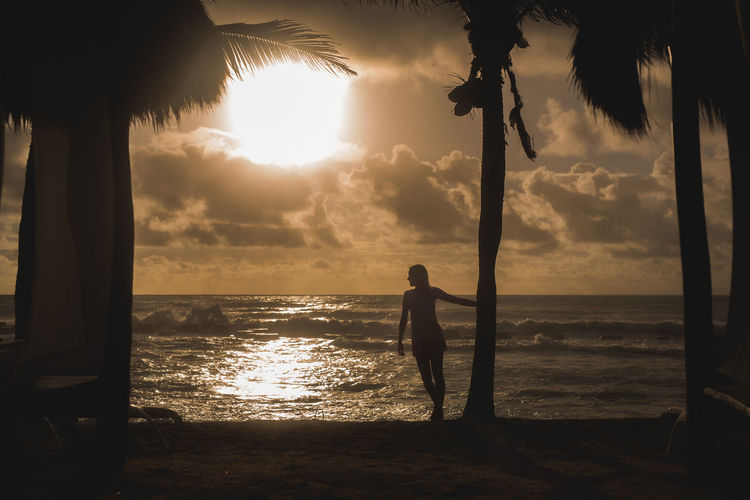 Beach Beauty In Nature Full Length Horizon Over Water Leisure Activity Nature Ocean One Person Outdoors Palm Tree Real People Scenics Sea Silhouette Sky Standing Sun Sunset Tranquil Scene Tranquility Tree Tree Trunk Vacations Water Weekend Activities