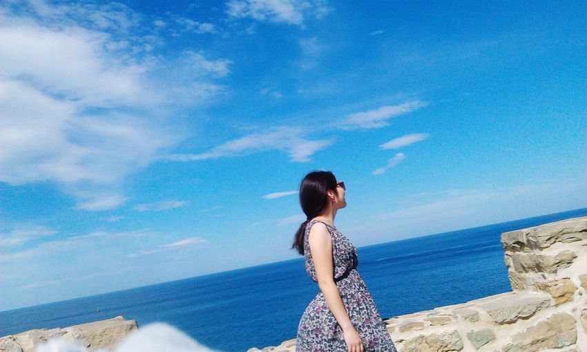 Woman standing by retaining wall against sea