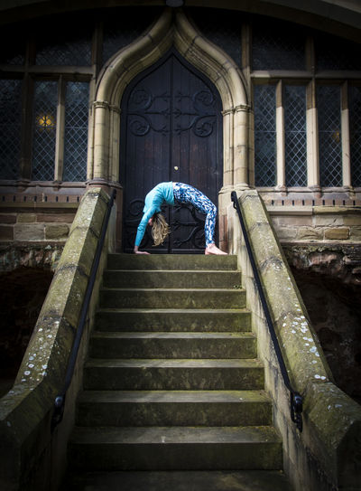 Young woman in bridge position practicing yoga on staircase against church