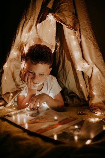 Blondy preschooler boy reads a book in hut at home with garlands and lights at night