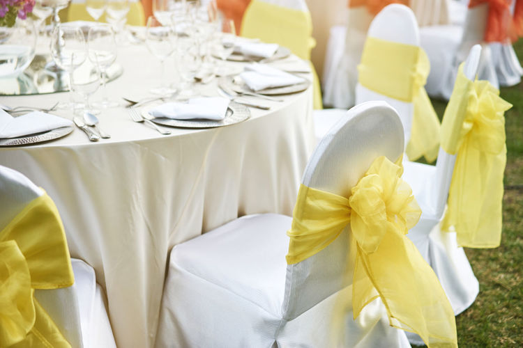 The wedding reception dinner table with spandex white cover chairs with yellow organza sash Banquet Beautiful Dinner Reception Venue Arrangement Bouquet Celebration Ceremony Chairs And Tables Decoration Dining Event Flower Glass Luxury Marriage  No People Outdoors Setting Sunset Table Wedding Wineglass Yellow Color
