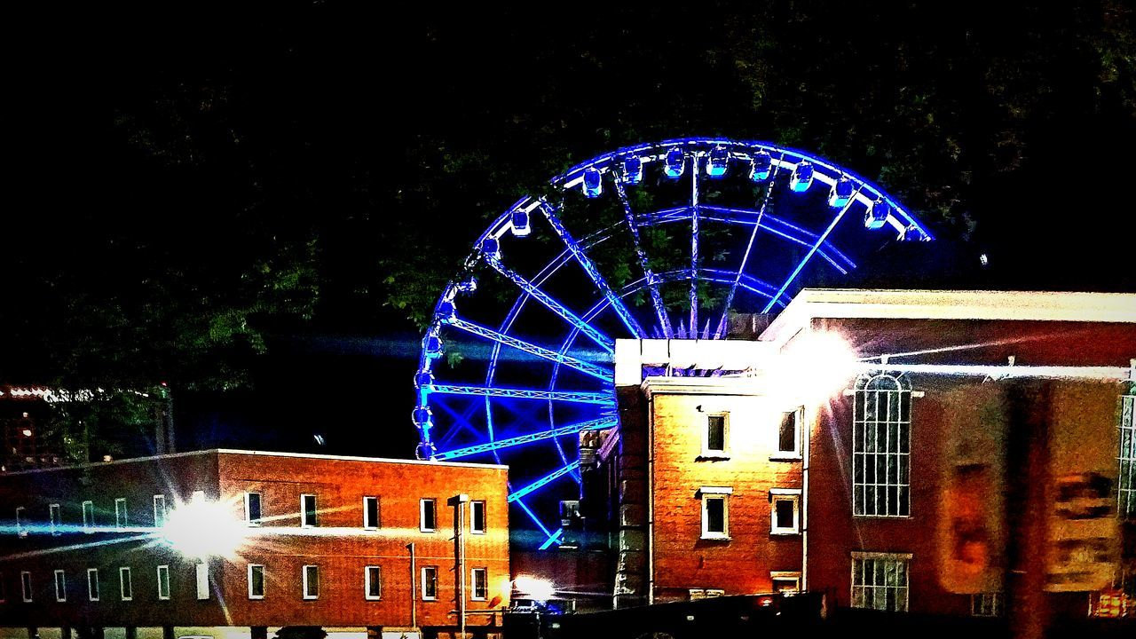 night, illuminated, amusement park, arts culture and entertainment, built structure, architecture, no people, outdoors, building exterior, amusement park ride, low angle view, ferris wheel, blue