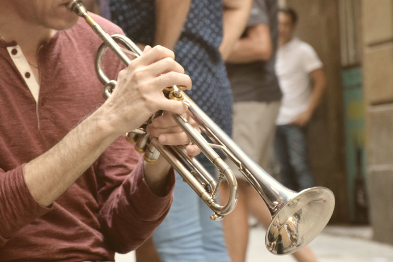 Playing the trumpet in the middle of the street Live Music Arts Culture And Entertainment Close-up Day Focus On Foreground Holding Human Hand Indoors  Men Midsection Music Musical Instrument Musician Performance Playing Real People Saxophone Skill  Standing Togetherness Trump Wind Instrument