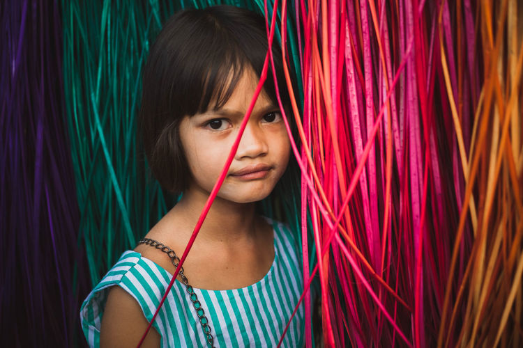 Portrait Of Girl By Colorful Curtain