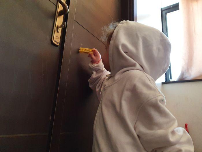 Rear view of daughter drawing against door