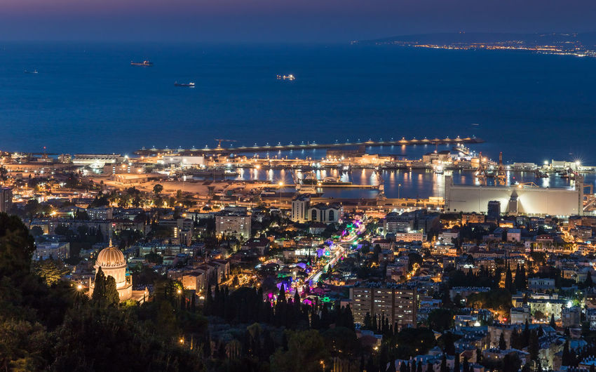 High angle view of illuminated city by sea against sky at night