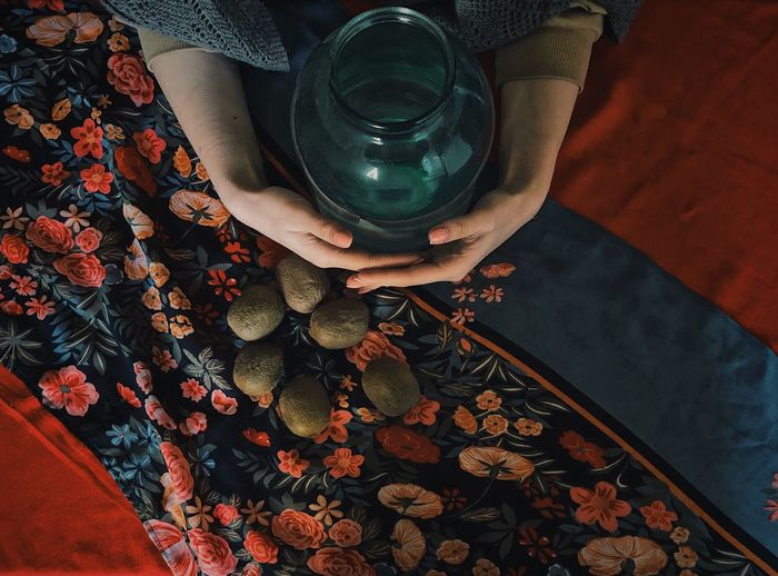Cropped hand of woman holding container with kiwi on floor