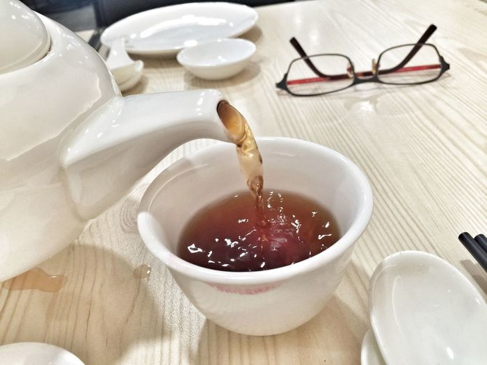 Close-Up Of Chinese Tea Being Poured In Cup On Table