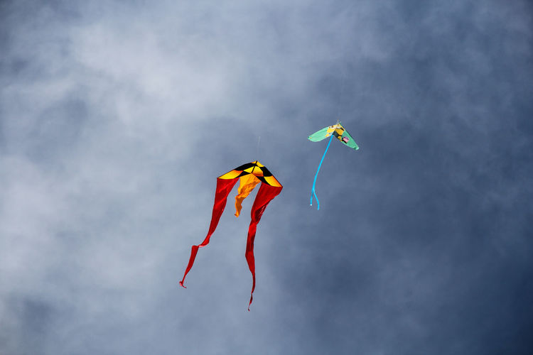 Low angle view of kites flying against sky