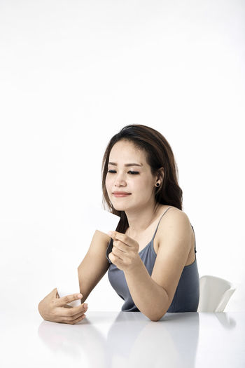 Asian woman shopping online studio shot on white background, for online shopping, technology and internet concept, Thai Studio Shot 30-34 Years Shopping Online  Young Female Happy Asian  Laptop Beautiful Internet Attractive Smile person Computer People Portrait Holding Phone Beauty Mobile Pretty Technology Payment Adult Using Lifestyle Cheerful Purchase Business Wireless Lady Chinese Fashion Looking Smartphone Japanese  Korean Credit Card Empty Text Copy Space White Background One Person Indoors  Front View Cut Out Young Adult Young Women Casual Clothing Women Sitting Waist Up Gesturing Hair Lifestyles Communication Hairstyle