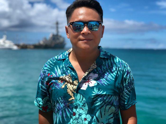 Portrait of man wearing sunglasses standing against sea