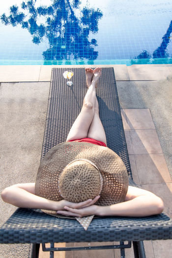 Midsection of woman sitting at swimming pool