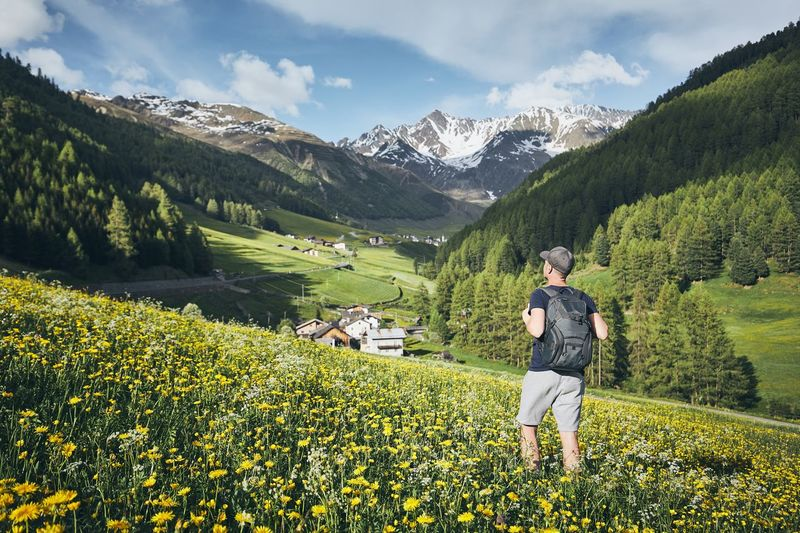 Young man (tourist) with backpack in nature. Village in mountains valley in Alps, Italy. Exploring Hiking Man Tourist Travel Trekking Vacations Beauty In Nature Blooming Countryside Journey Landscape Leisure Activity Lifestyles Mountain Mountain Range Nature Real People Rear View Rural Scene Scenics - Nature Tourism Tranquility Valley Village