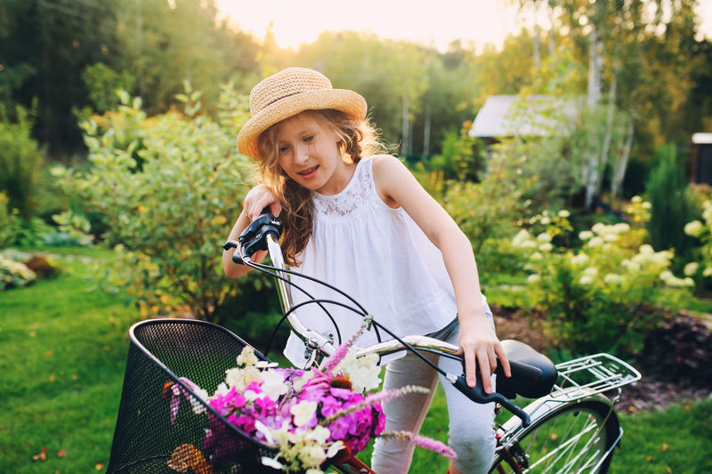 Smiling girl riding bicycle against trees