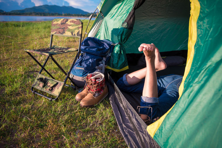 Close up of woman legs relaxing in camping tent with mountain lake and meadow and grass field background. Lifestyles and People concept. Camping and picnec theme. Green natural and summer travel theme Camping Traveling Woman Adult Adventure Camping Casual Clothing Day Full Length Grass Land Legs Leisure Activity Lying Down Lying On Back Nature Outdoors People Plant Relaxation Tent Tents Women Young Adult Young Women