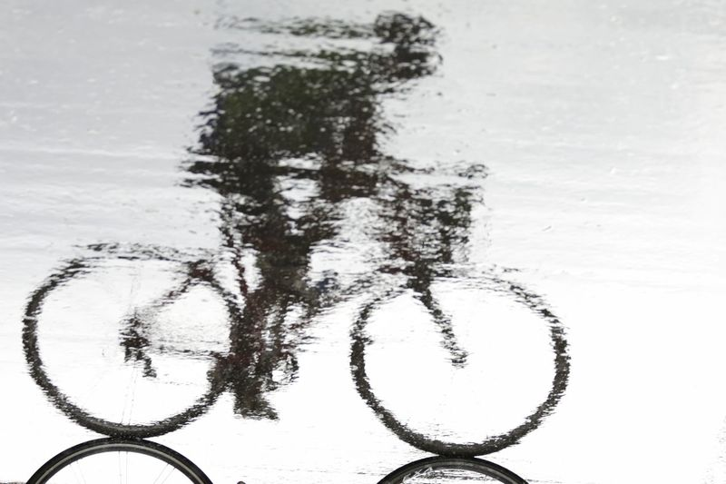 Person riding bicycle reflecting on wet road during rainy season