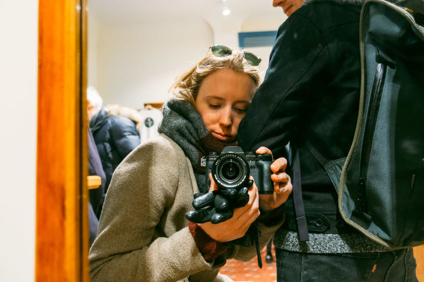 Camera - Photographic Equipment Casual Clothing Child Digital Camera Focus On Foreground Holding Indoors  Leisure Activity Lifestyles Men Mirror People Photographer Photographic Equipment Photography Themes Real People Reflection Standing Technology Two People Women