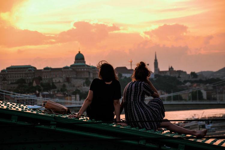Rear View Of Female Friends Sitting On Liberty Bridge In City Against Orange Sky