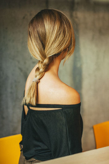 Rear view of woman with braided hair siting on chair against wall