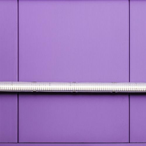 Low angle view of illuminated lighting equipment on purple wall