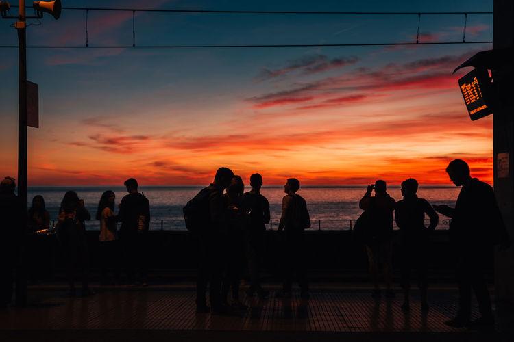 Silhouette people by sea against orange sky