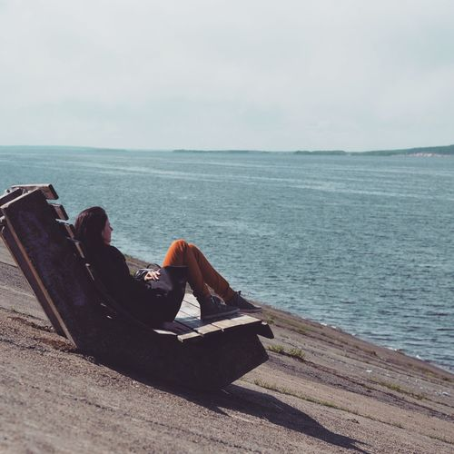 Woman Sitting On Wood By Sea Against Sky