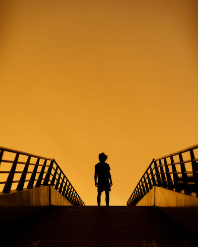 Silhouette man standing on staircase against sky during sunset