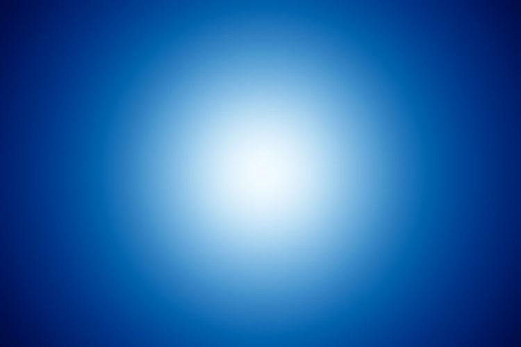Defocused image of illuminated lights against blue sky