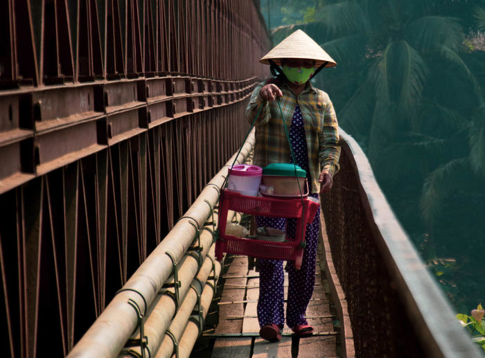 Woman wearing hat carrying containers while walking on footbridge