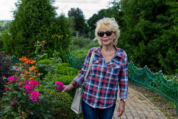 Mature woman with sunglasses standing by plants