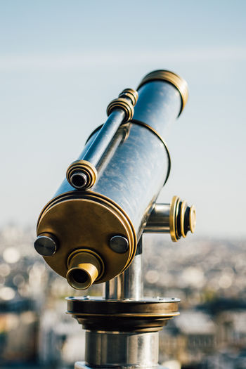 Close-up of hand-held telescope against sky