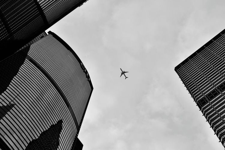 Low Angle View Of Airplane Flying Over Buildings Against Sky