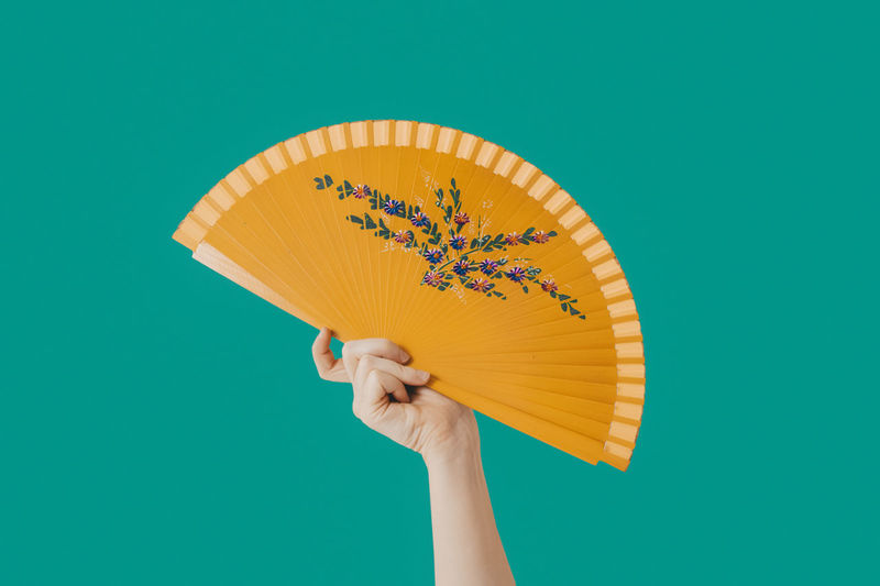Close-up of person holding umbrella against blue background