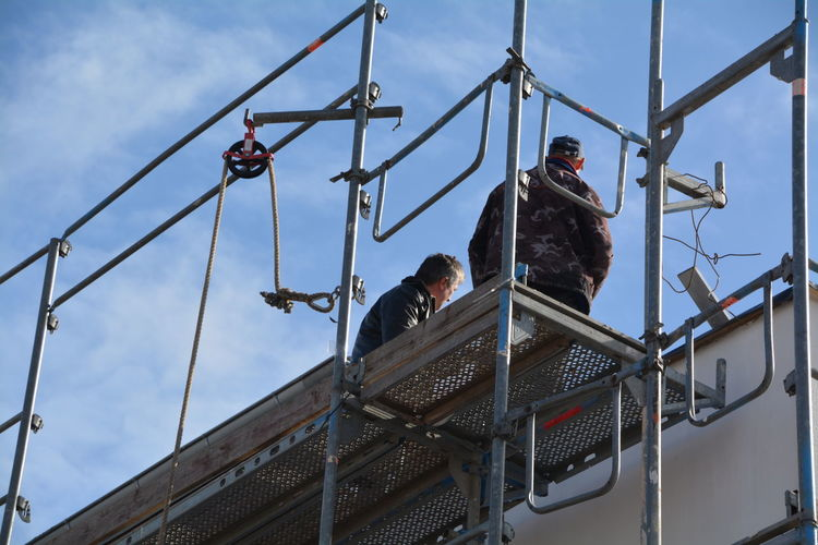 Low Angle View Of Workers Standing On Metallic Platform Against Sky