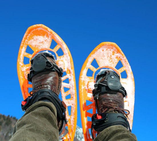 two modern orange snowshoes and blue sky on background 2 Leg Man Snowshoe Adventure Blue Sky Body Part Extreme Sport Extreme Sports Guy Legs Mountains Orange Color Outdoors person Relax Snowshoe Trip Snowshoeing Snowshoes Snowshoes Sport Sport Sports Sports Clothing Two Objects Two People