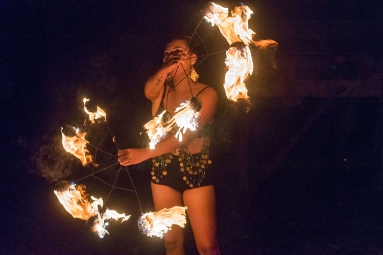 Young woman performing with fire at night