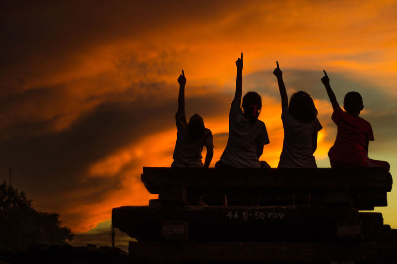 Adult Architecture Arms Raised Belief Cloud - Sky Group Of People Human Arm Leisure Activity Men Nature Orange Color Outdoors People Real People Religion Silhouette Sky Spirituality Sunset Togetherness Women