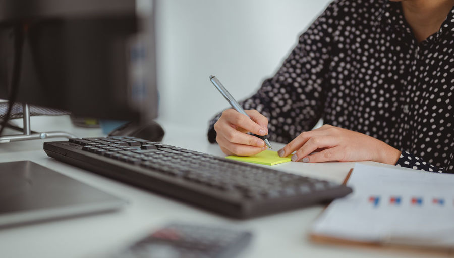 Midsection of woman writing on adhesive note at desk