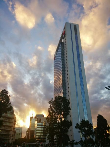 Sunset Cloud - Sky Low Angle View Sky Modern Skyscraper City Architecture Outdoors Building Exterior City Life Sunlight Clouds Modern Cityscape City Day Sunset Clouds And Sky City Street Sunset And Clouds  Sunset Colors Multi Colored Lights Illuminated