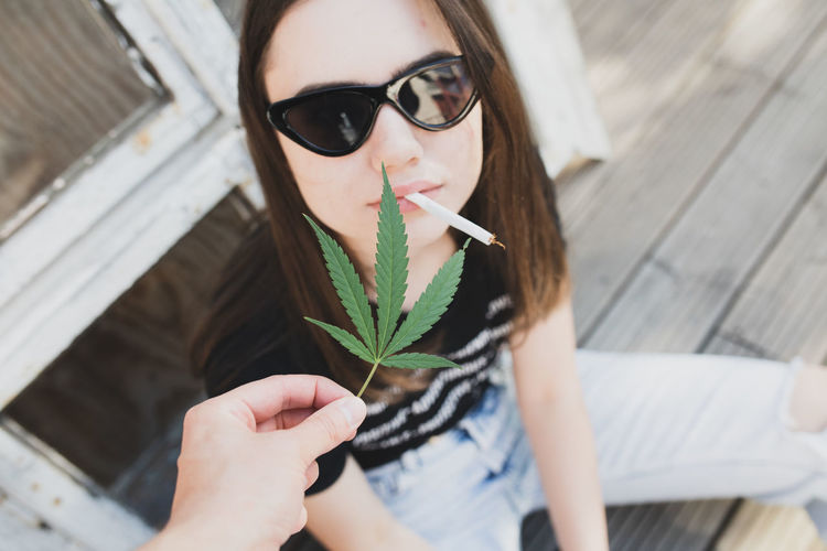 Cropped hand holding marijuana by young woman
