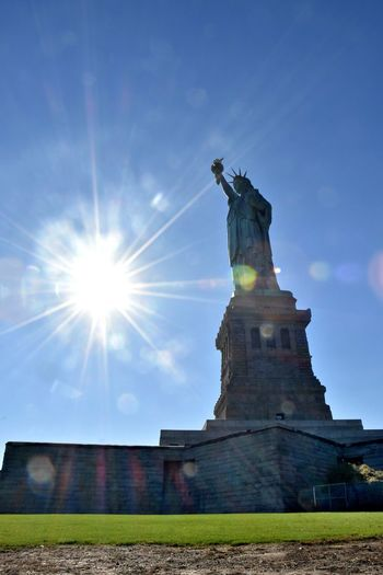 Liberty Island Freedom Independence Statue Of Liberty Built Structure Day History Human Representation Lady Liberty Lens Flare Light Flare Low Angle View No People Representation Sculpture Sky Statue Sun Sunbeam Sunlight Travel Destinations