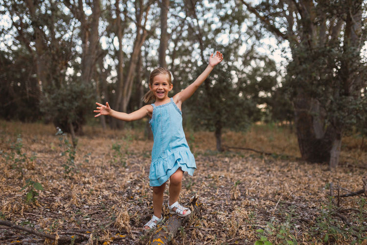 Portrait of happy girl playing in forest