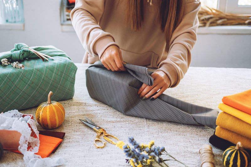 Midsection of woman wrapping gift with textile