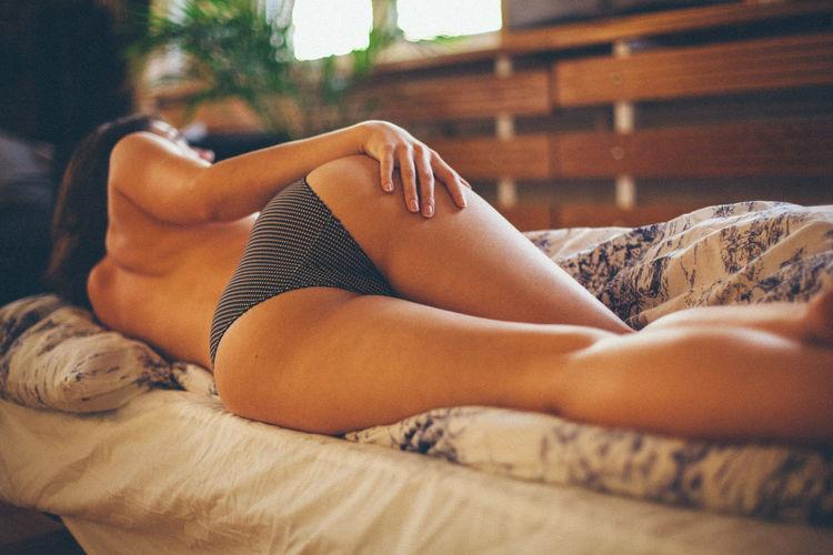 Young woman in bikini lying on bed at home