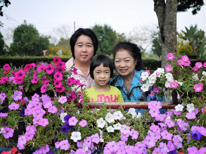 Portrait of family against blooming flowers